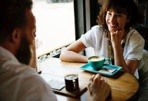 un homme de dos et une jeune femme prennent un café